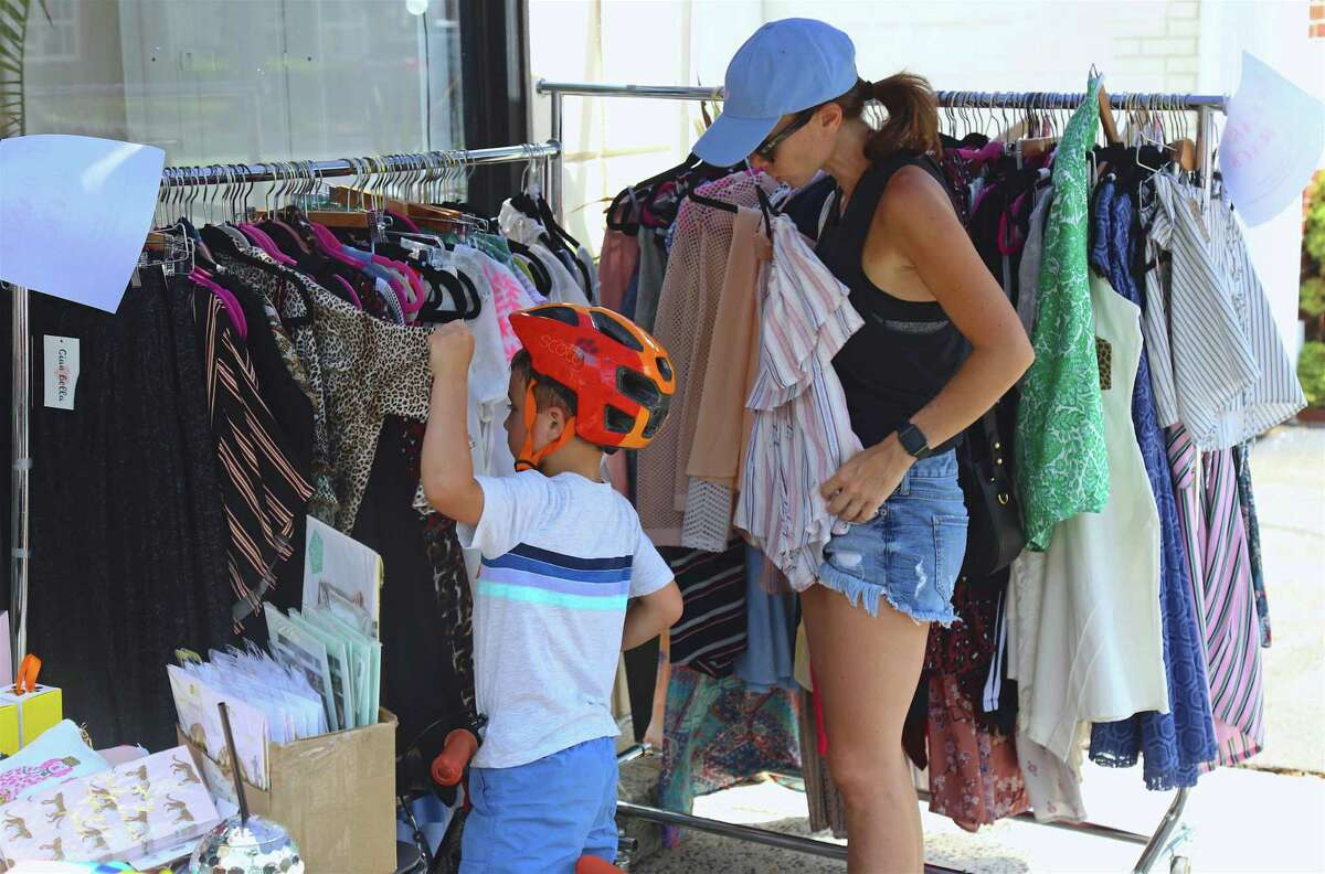 Nicole Barrato of Fairfield and her son, Cole, 5, check out the merchandise at Ciao Bella at the annual Fairfield Sidewalk Sale & Street Fair on Saturday, July 20, 2019, in Fairfield, Conn.