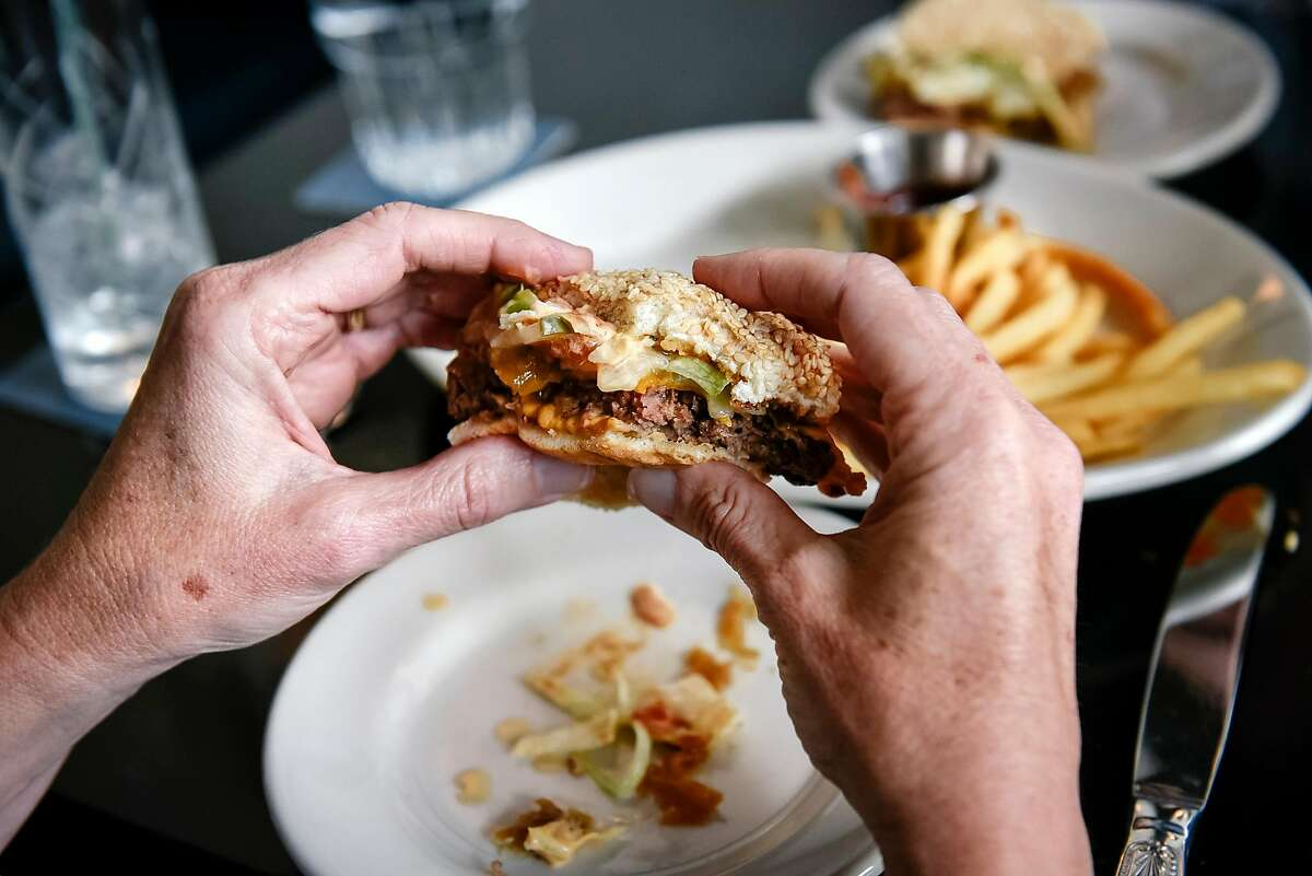 Laura Hill, of San Francisco, digs into an Impossible Burger at Violet's restaurant in San Francisco, Calif., on July 21st, 2019. Impossible Foods is distributing Impossible Burgers to independent restaurants again after a two-month dry spell, which coincided with its expansion to Burger Kings nationwide.