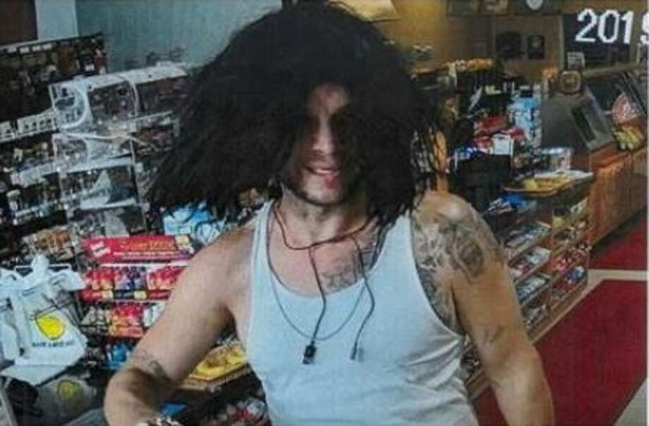A man wearing a long, black wig is seen in surveillance stills from a gas station where authorities say he and another man left a Dodge Ram they stole from a Porter apartment complex two days before. Photo: Courtesy Of The Montgomery County Sheriff's Office