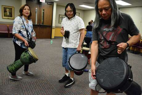 George Ty, left, with his son Victor and wife Theresa, bring their own instruments to the drum circles at Friendswood Public Library. The sessions feature an assortment of percussion instruments, including tambourines, shakers, congas and a type of drum called a djembe.