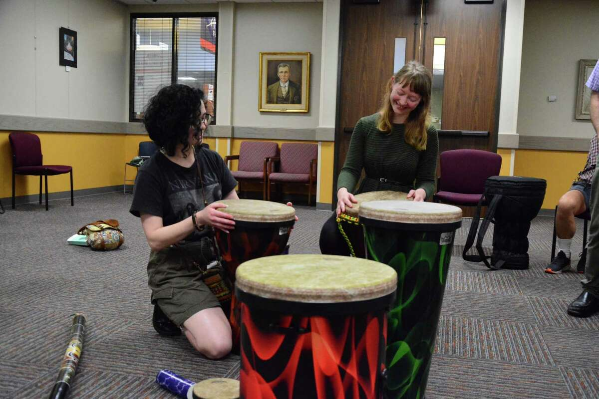 Hannah Philibert, 21, left, and Alyssa Morgan, 29, choose their instruments a recent drum circle hosted by the Friendswood Public Library.
