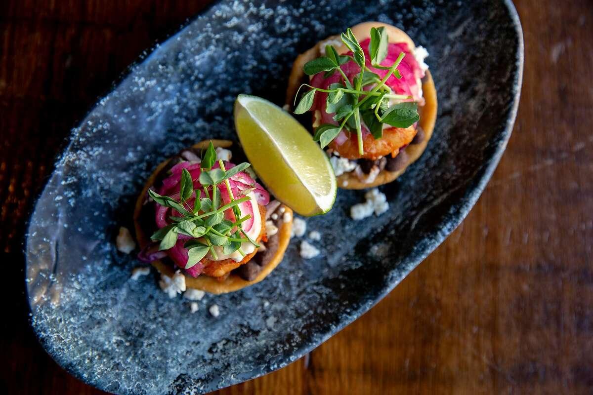 The gluten-free honey garlic shrimp sopes (mango feta salsa verde, black bean, chili lime aioli, pepitas, island cabbage, yam tortilla) at alaMar Kitchen & Bar, Thursday, July 18, 2019, in Oakland, Calif.