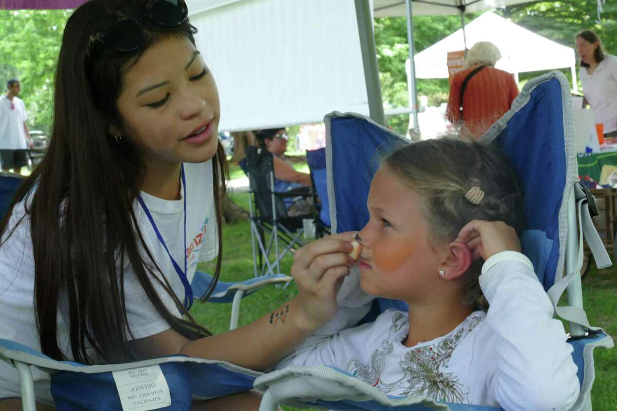 Emily Vides from the National Charity League's Nutmeg Chapter transforms Chadee into a tiger at Summerfest in Ballard Park on July 20.