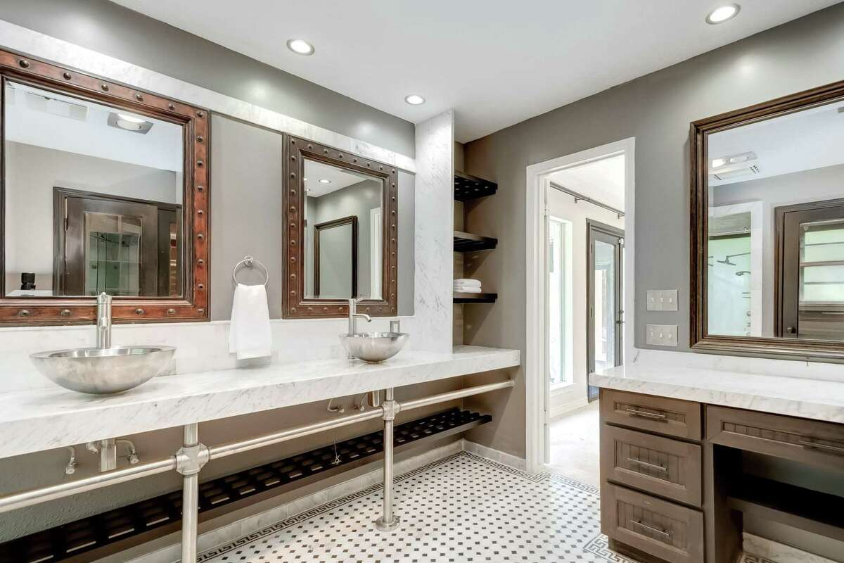 The master bathroom in this Kingwood was finished with Carrara marble and a chrome base for the sinks.