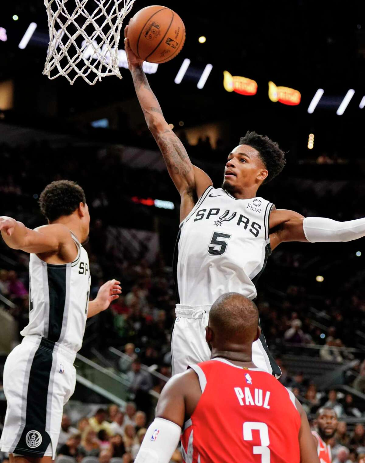San Antonio Spurs' Dejounte Murray (5) grabs a rebound next to teammate Bryn Forbes, left, and Houston Rockets' Chris Paul (3) during the second half of an NBA preseason basketball game, Sunday, Oct. 7, 2018, in San Antonio. (AP Photo/Darren Abate)