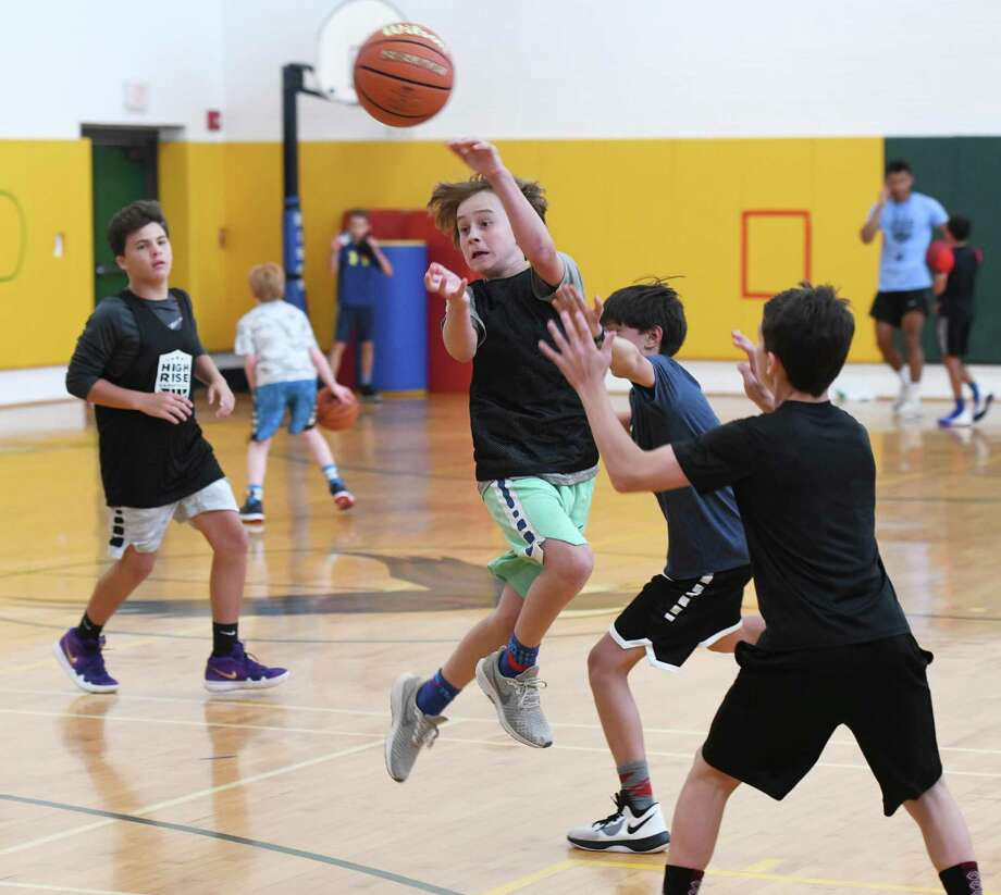 Calvin Walker, 12, makes an acrobatic pass during a game at High Rise Basketball's summer camp at Eagle Hill School in Greenwich, Conn. Monday, July 22, 2019. The camp has been in action at Eagle Hill since 2011, helping kids ages 7 through 15 refine their basketball skills through a series of drills, conditioning exercises, and competitive league-style games. Photo: Tyler Sizemore / Hearst Connecticut Media / Greenwich Time