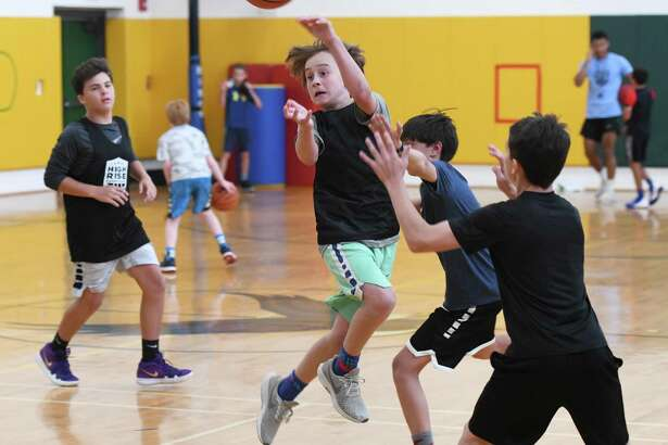 Calvin Walker, 12, makes an acrobatic pass during a game at High Rise Basketball's summer camp at Eagle Hill School in Greenwich, Conn. Monday, July 22, 2019. The camp has been in action at Eagle Hill since 2011, helping kids ages 7 through 15 refine their basketball skills through a series of drills, conditioning exercises, and competitive league-style games.
