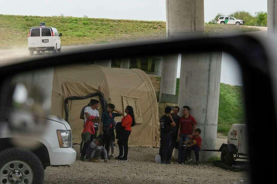 Migrant families wait for Border Patrol agents under the Anzalduas Bridge in McAllen, Texas on June 21, 2019. Photo: Washington Post Photo By Carolyn Van Houten / The Washington Post