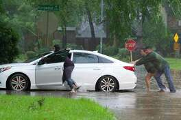 Residents push a stalled car as thunderstorms hit the Kingwood area flooding parts of Kingwood Drive, Tuesday, May 7, 2019, in Kingwood.