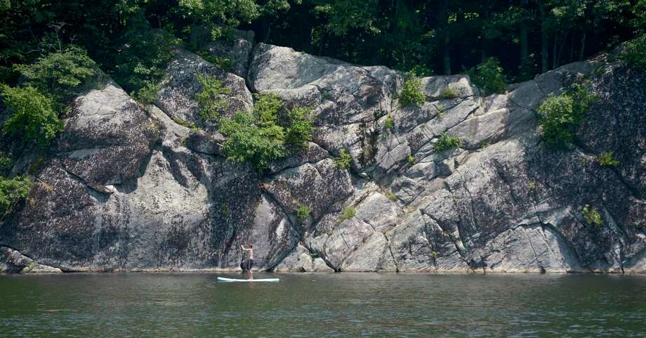 A paddle boarder glides by the cliffs on Mamanasco Lake. that are located in Richardson Park. Monday, July 22, 2019, in Ridgefield, Conn. Photo: H John Voorhees III / Hearst Connecticut Media / The News-Times