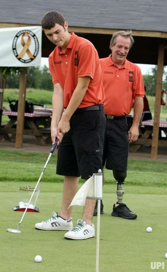 Shawn Hornbeck, left, the boy who was held captive for over four years and finally freed in January from the St. Louis area apartment of Michael Devlin, makes a putt as his dad Craig Akers watches during the Shawn Hornbeck Foundation Golf Tournament at Gateway National Golf Links in Madison, Illinois on July 19, 2007. Hornbeck also celebrated his 16th birthday at the event. Photo: UPI Photo | Bill Greenblatt