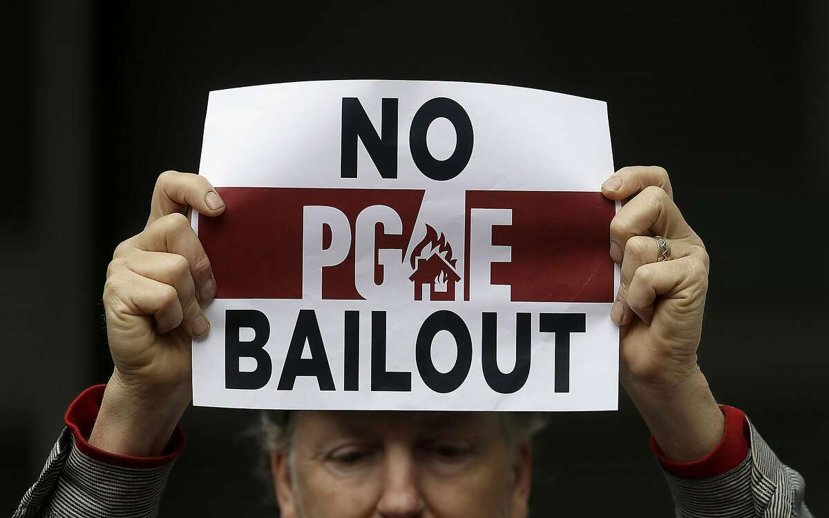 """FILE - In this Jan. 28, 2019 photo, a man holds a sign at a rally before a California Public Utilities Commission meeting in San Francisco. A Wednesday, July 10, 2019, report in the Wall Street Journal says Pacific Gas & Electric, which is blamed for some of California's deadliest recent fires, knew for years that dozens of its aging power lines posed a wildfire threat but avoided replacing or repairing them. PG&E says it disagrees with the Journal's conclusions but says it�s """"taking significant actions to inspect, identify, and fix"""" safety issues. (AP Photo/Jeff Chiu, File)"""