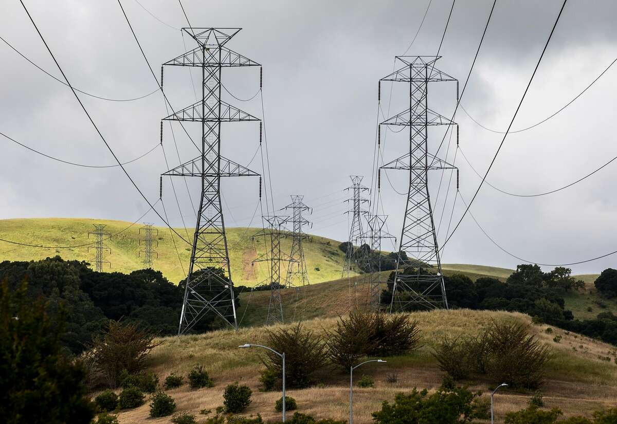 High-voltage power transmission lines owned by PG&E are seen stretched across an area od San Ramon. California's electricity prices are growing so high that they threaten the state's ability to convince enough people to ditch fossil fuel-powered cars and appliances, new research says.