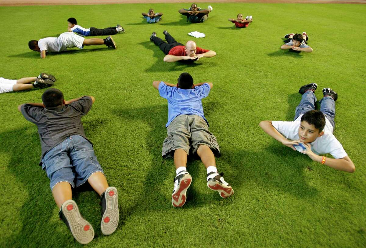 """Astros Assistant Athletic Trainer, Rex Jones (in the center with red shirt) leads a group of kids from the Boys and Girls Club to stretching exercises during the 2009 National """"PLAY"""" event, hosted by the Houston Astros, at Minute Maid Park. PLAY stands for Promoting a Lifetime of Activity for Youth and is a public awareness campaign of the Professional Baseball Athletic Trainers Society (PBATS). ( Karen Warren / Chronicle )"""