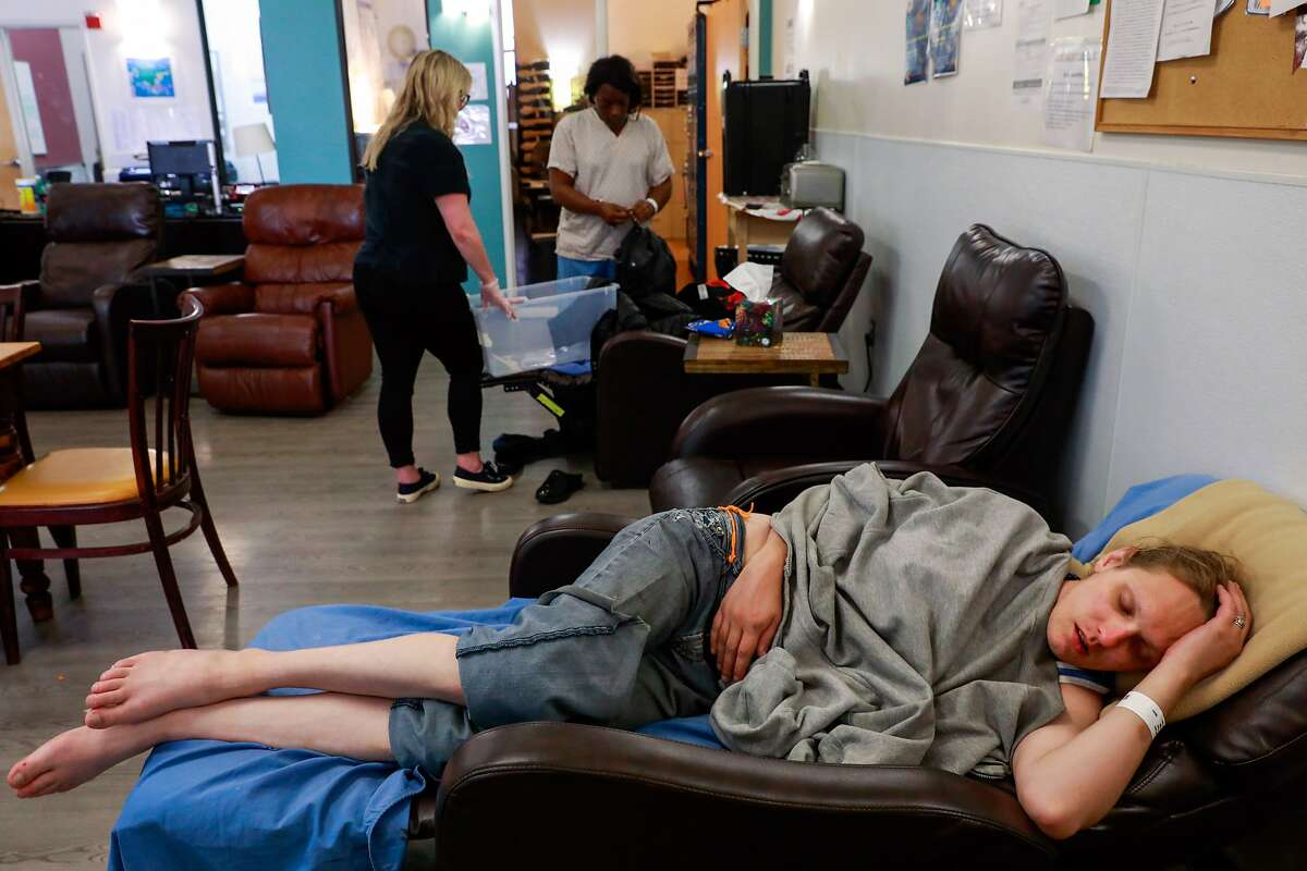Lindsey Cassidy (bottom) sleeps as Breanna Blueford (top,right) gets her belongings together at the Dore Urgent Care clinic which is a crisis drop-in center for mental health needs in San Francisco, California, on Monday, June 10, 2019. Supervisors Matt Haney and Hillary Ronen have proposed a sweeping ballot measure to overhaul the city's mental health care system.