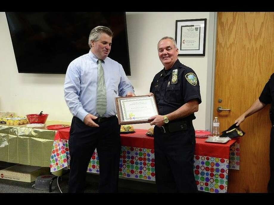 Branford police Capt. Ray Dunbar, right, was honored by Republican First Selectman Jamie Cosgrove, left, last week in connection with Dunbar's retirement from the Police Department after 38 years. But they may spend more time together after Dunbar's retirement: the Democratic Town Committee endorsed Dunbar to run for selectman on Tuesday, July 16, 2019. Photo: Branford Police Department / Contributed Photo