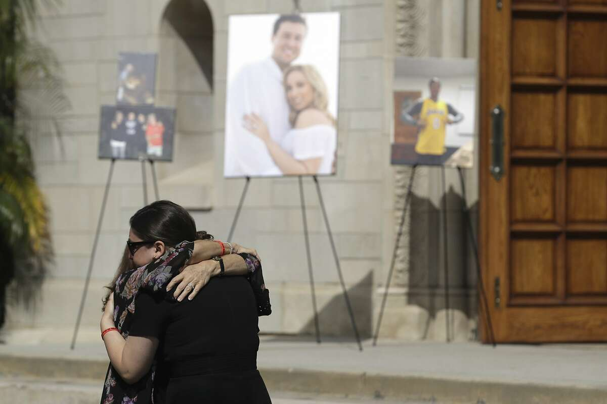 Mourners embrace during a memorial for Los Angeles Angels pitcher Tyler Skaggs at the St. Monica Catholic Church Monday, July 22, 2019, in Los Angeles. (AP Photo/Marcio Jose Sanchez)