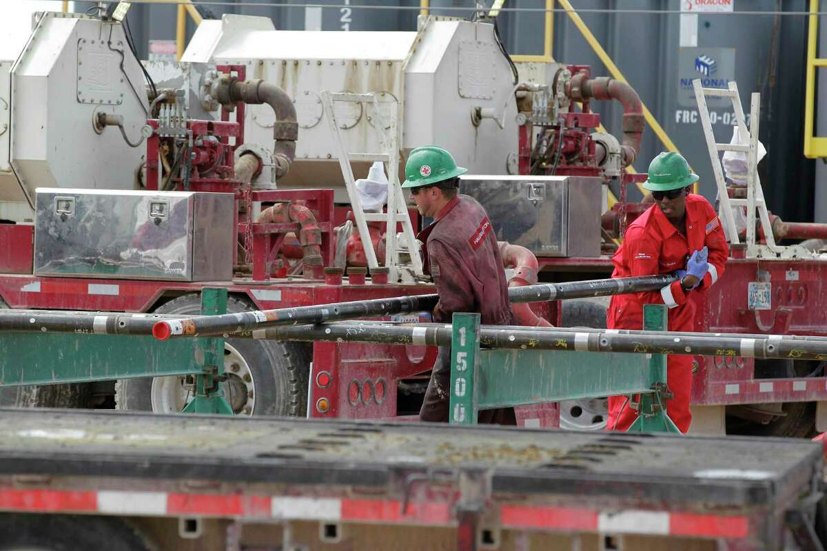 In this file photo, Halliburton employees move pipe at a three wellhead fracking site. Oil field services companies appear to have turned the corner after getting hard hit by the pandemic-driven oil bust.