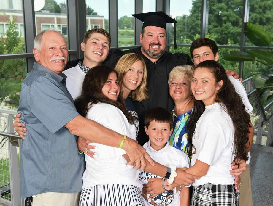 Former Southern Connecticut State University football alum Joe Andruzzi poses with his family on Monday in New Haven. Andruzzi received his undergraduate degree in special education 23 years after completing his playing career with the Owls. Photo: Isabel Chenoweth / SCSU / SCSU