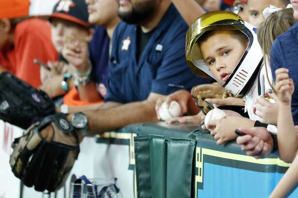 A kid wears an astronaut helmet during batting practice as the Houston Astros will hosted Apollo 11 Night, a special night celebrating the 50th anniversary of the Apollo 11 Mission and the first landing on the moon before the start of an MLB baseball game at Minute Maid Park, Monday, July 22, 2019.