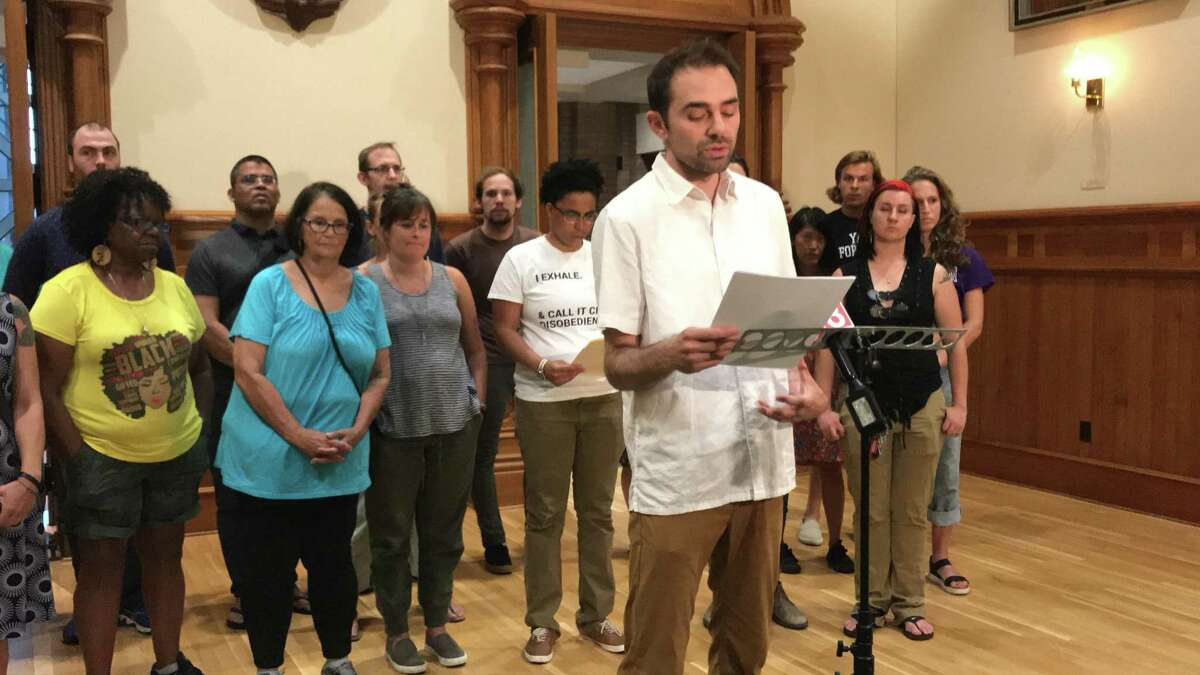 Activist Aaron Jafferis reads a letter from Civilian Review Board activists raising concerns with the process by which Mayor Toni Harp nominated 11 people to that board in City Hall on July 22, 2019.