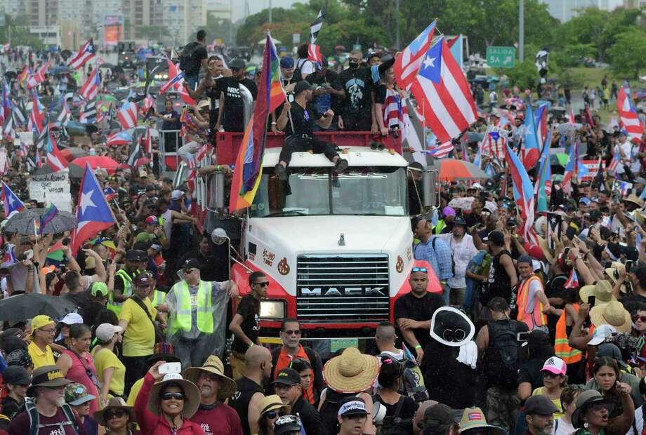 Puerto Rican singer Ricky Martin, front atop truck, participates with other local celebrities in a protest demanding the resignation of governor Ricardo Rossello in San Juan, Puerto Rico, Monday, July 22, 2019. Protesters are demanding Rossello step down for his involvement in a private chat in which he used profanities to describe an ex-New York City councilwoman and a federal control board overseeing the island's finance. (AP Photo/Carlos Giusti) Photo: Carlos Giusti / Copyright 2019 The Associated Press. All rights reserved.