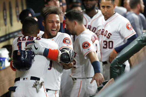 Houston Astros Yuli Gurriel (10) is hugged by Tony Kemp (18) in the dugout as they celebrated his two-run home run during the third inning of an MLB baseball game at Minute Maid Park, Monday, July 22, 2019.