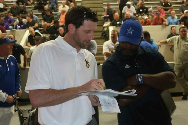 Deer Park head football coach Austin Flynn confers with a Baytown Sterling coach at the recent Referee Selection meeting. The annual preseason prediction by Dave Campbell's magazine believes both schools will miss the playoffs.