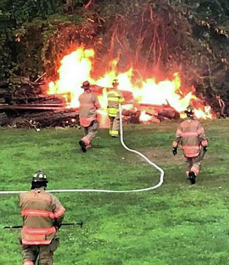 "Members of the Brookfield Volunteer Fire Co. extinguished a brush fire started by lightning on Monday, July 22, 2019. ""Units arrived to find a substantial fire in the rear yard of an Ina Street house from a lightning strike. A tree was hit and the lightning traveled down to a large pile of dead trees and brush from last year's Macroburst. E-4,"" the department posted on its Facebook page. Photo: Brookfield Volunteer Fire Co."