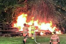 """Members of the Brookfield Volunteer Fire Co. extinguished a brush fire started by lightning on Monday, July 22, 2019. """"Units arrived to find a substantial fire in the rear yard of an Ina Street house from a lightning strike. A tree was hit and the lightning traveled down to a large pile of dead trees and brush from last year's Macroburst. E-4,"""" the department posted on its Facebook page."""