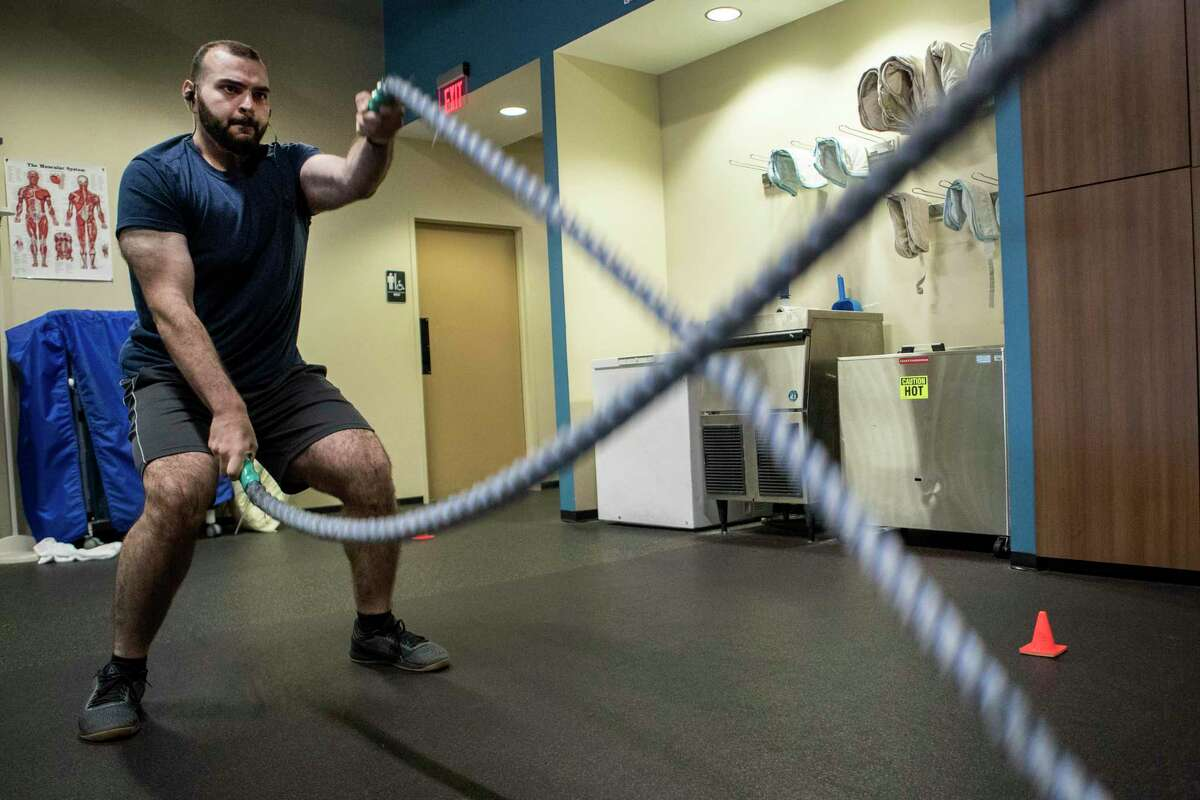 Amer Ismail works out at the Memorial Hermann IRONMAN Performance Lab on Friday, July 19, 2019, in Houston. A hot dog eating challenge at an Astros game led him to choose a healthier lifestyle. He has lost 200 pounds in the last few years. He is now weighing in at 270, with the goal to lose 60 more pounds.