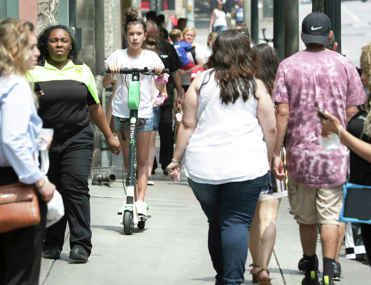 A young girl rides a scooter on a crowded side walk on Commerce St. on Thursday, May, 30, 2019. City Council voted Thursday to ban riding scooters on sidewalks.