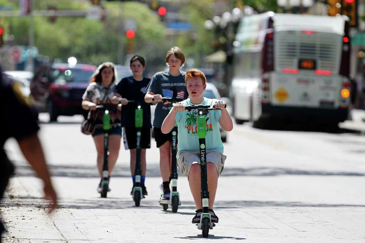Scooters cruise down the street in San Antonio. Riding in the street is now the only legal option in Houston.
