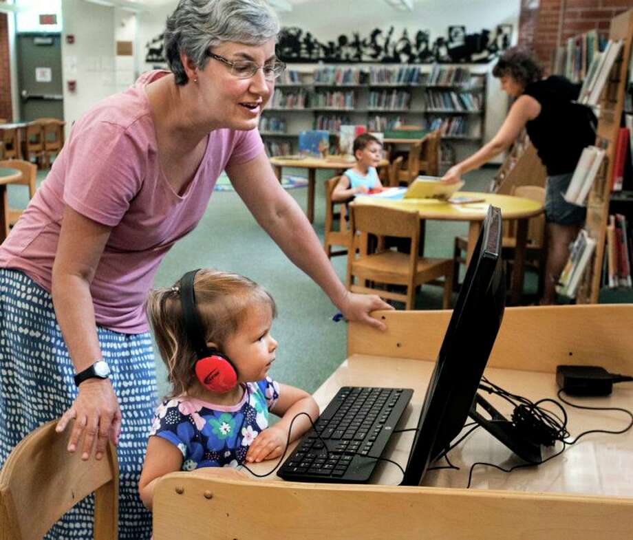 Mitchell branch librarian, Sharon Lovett-Graff helps Lydia Anderson, 3, with the computer while mom, Laura Anderson, helps brother Ethan Anderson, 4 1/2, select books. The Andersons are from New Haven. Photo: Melanie Stengel / C-Hit.org