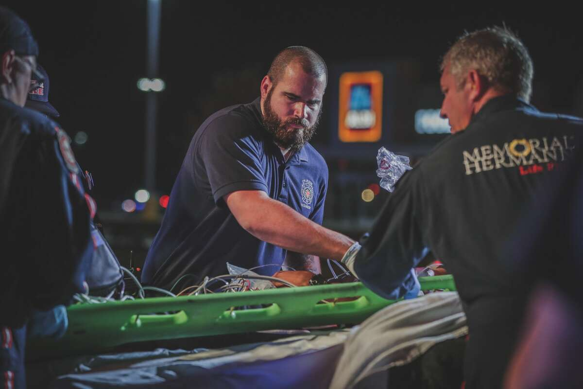 Paramedics with Cy-Fair Volunteer Fire Department and Memorial Hermann Life Flight tend to a young man found shot in the head along Fry Road on Monday, July 22, 2019.