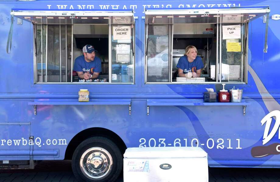 Drew Kaplan, left, and Anna Lewis, of DrewbaQ, were dishing out bbq at Food Truck Thursday at Kennedy Park, in Danbury, Conn, June 27, 2019. New Milford is looking to create a food truck ordinance that would allow food trucks to be at area businesses in the town. Photo: H John Voorhees III / Hearst Connecticut Media / The News-Times
