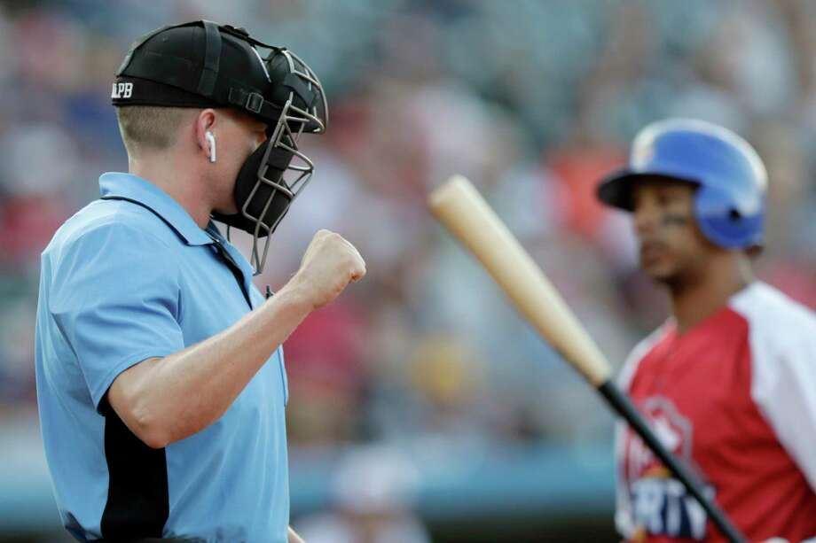 Home plate umpire Brian deBrauwere, left, calls a strike given to him by a radar system over an earpiece as Liberty Division's Tyler Ladendorf, right, of the High Point Rockers, strikes out to Freedom Division's Mitch Atkins, of the York Revolution, during the first inning of the Atlantic League All-Star minor league baseball game, Wednesday, July 10, 2019, in York, Pa. deBrauwere wore the earpiece connected to an iPhone in his ball bag which relayed ball and strike calls upon receiving it from a TrackMan computer system that uses Doppler radar. The independent Atlantic League became the first American professional baseball league to let the computer call balls and strikes during the all star game. (AP Photo/Julio Cortez) Photo: Julio Cortez, Associated Press / Copyright 2019 The Associated Press. All rights reserved.