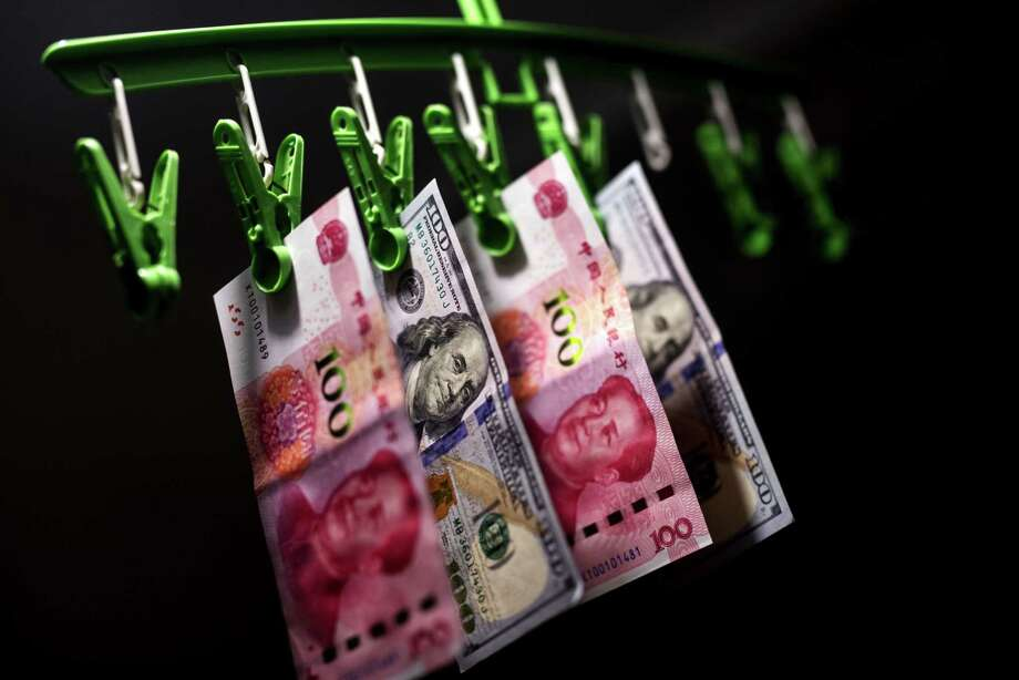 Chinese one-hundred yuan banknotes and U.S. dollar banknotes in Hong Kong on April 15, 2019. Photo: Bloomberg Photo By Paul Yeung. / © 2019 Bloomberg Finance LP
