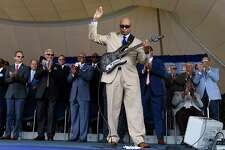 Former New York Yankees player Bernie Williams, foreground, performs during a National Baseball Hall of Fame induction ceremony at the Clark Sports Center, Sunday, July 21, 2019, in Cooperstown, N.Y. (AP Photo/Hans Pennink)