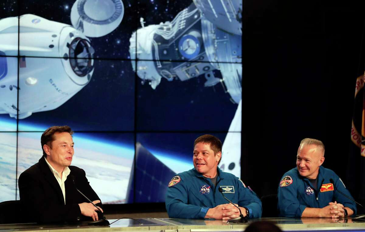 Elon Musk, left, CEO of SpaceX, with NASA astronauts Bob Behnken, center, and Doug Hurley, right, during a news conference after the SpaceX Falcon 9 Demo-1 launch at the Kennedy Space Center in Cape Canaveral, Fla., Saturday, March 2, 2019. (AP Photo/John Raoux)