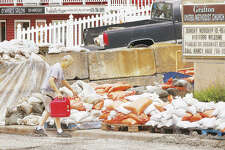 Long-time Grafton resident Gary VonDell, the owner of VonDell Gallery and Studios in Wood River, helps with cleanup efforts in downtown Grafton on June 20. Gov. J.B. Pritzker on Tuesday asked the Federal Emergency Management Agency to help state and local officials fully assess the damage caused by this year's flooding in preparation for a request for federal aid.
