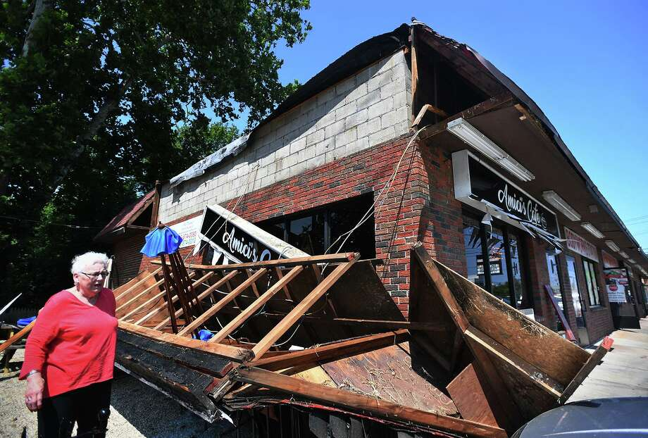 Amici's Cafe customer Janet Aldrich, of Milford, surveys the damage after a large wooden awning collapsed on picnic tables outside the business at 784 Boston Post Road in Milford, Conn. on Monday, July 22, 2019. Photo: Brian A. Pounds / Hearst Connecticut Media / Connecticut Post