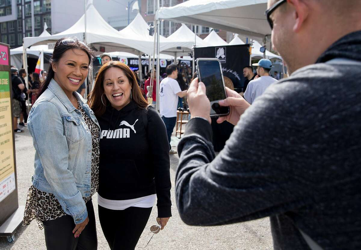 Freestyle artist Jocelyn Enriquez (left) poses for a picture with a fan during Undiscovered SF's creative night market in San Francisco, Calif. Saturday, July 20, 2019.