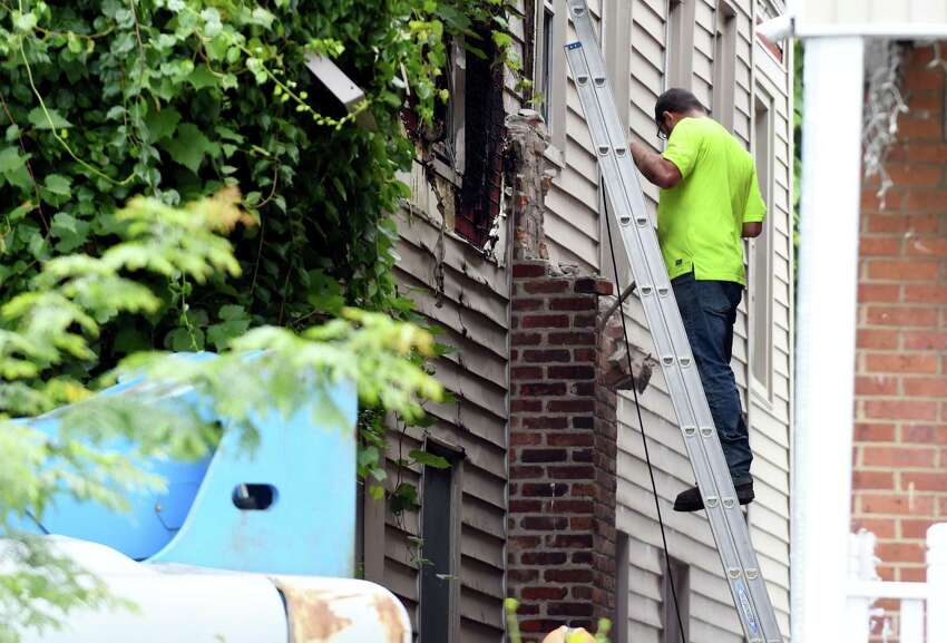 A city worker removes bricks from the chimney of blighted city-owned property at 792 Francis Ave. in Mont Pleasant on Tuesday, July 23, 2019, in Schenectady, N.Y. Neighbors complained to the city about the property for years and it is finally being torn down (Catherine Rafferty/Times Union)