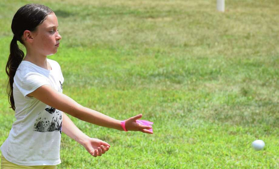Spectrum/Clatter Valley Park in New Milford was abuzz with activity the week of July 14-19, 2019, when Girl Scout day camp was held. Above, Lydia Hyde tosses a golf ball during a sports activity. Photo: Deborah Rose / Hearst Connecticut Media / The News-Times  / Spectrum