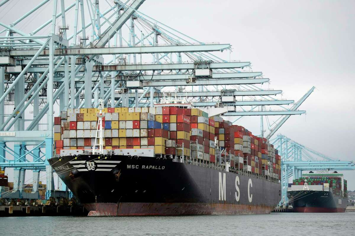 FILE - In this Wednesday, June 19, 2019, file photo, a cargo ship is docked at the Port of Los Angeles, in Los Angeles. The International Monetary Fund is downgrading its outlook for the world economy because of simmering international trade tensions. But at the same time, the fund is slightly boosting its forecast for U.S. economy in 2019, citing expectations that the Federal Reserve will cut interest rates. (AP Photo/Marcio Jose Sanchez, File)