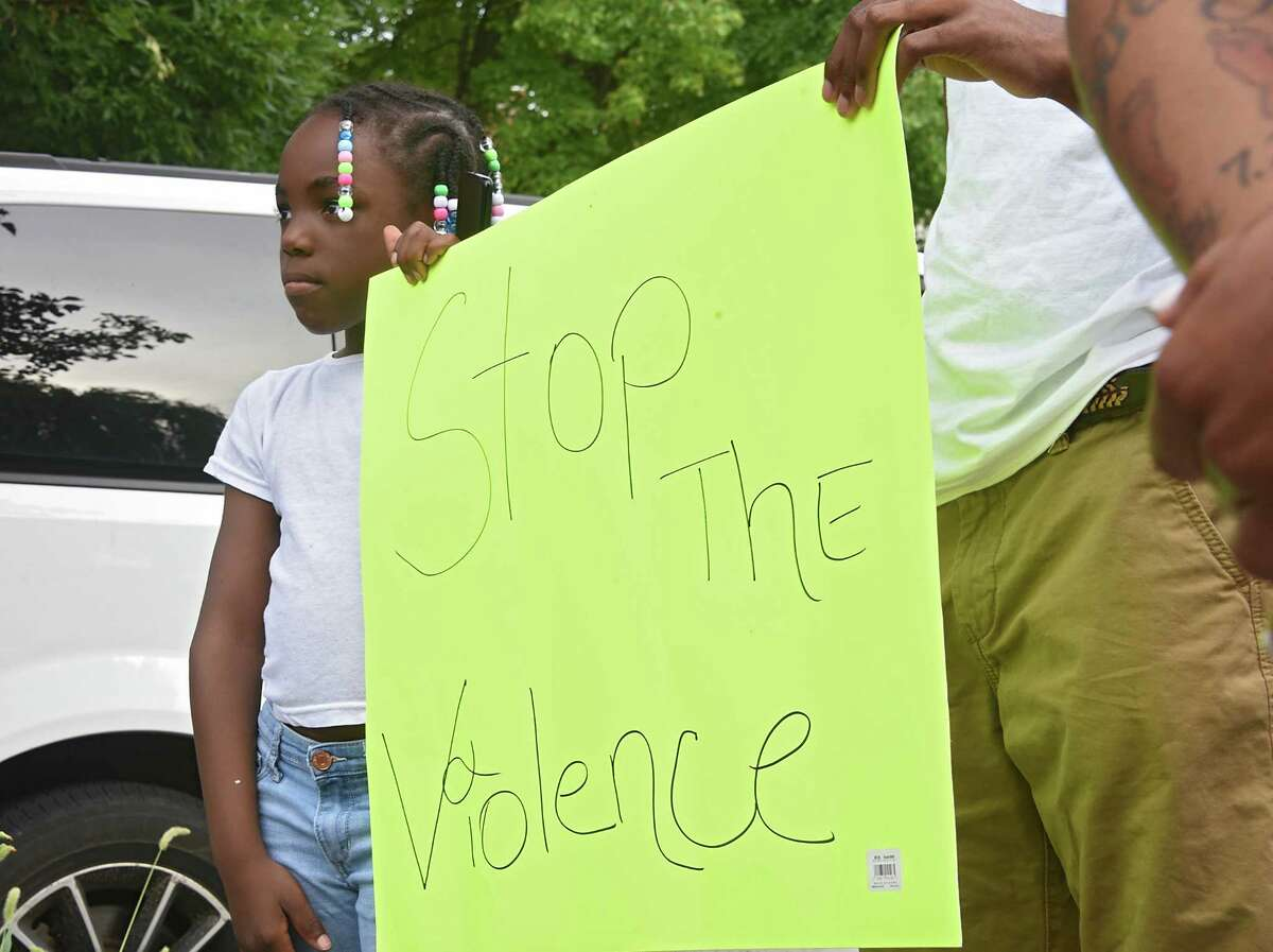 Angel Maria Stokes,7, holds a sign with her brother Shy'reed Wofford as anti-violence activists hold a rally at Third Avenue and Elizabeth Street near where a sleeping child was hit with a stray bullet last week on Tuesday, July 23, 2019 in Albany, N.Y. Albany 518 SNUG organized the gathering. (Lori Van Buren/Times Union)