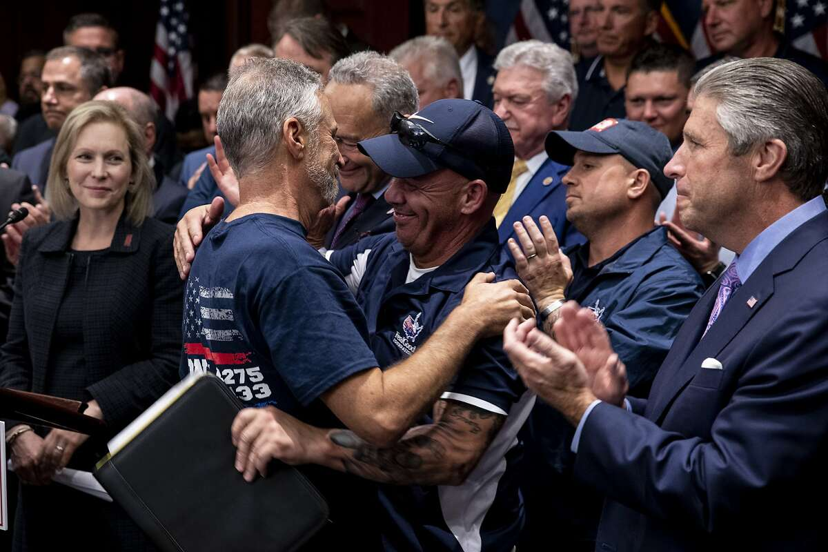 The comedian Jon Stewart embraces John Feal, an advocate, at a news conference after passage of legislation to extend aid to Sept. 11 emergency workers on Capitol Hill in Washington, July 23, 2019. Congress on Tuesday gave final approval to legislation that would extend lifetime compensation to emergency workers who became ill after the attacks. (Anna Moneymaker/The New York Times)