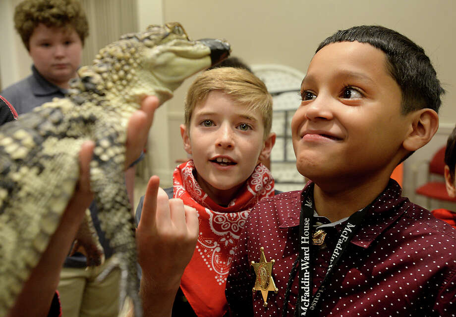 """Aaron Duarte (right) and Nash Campbell react as they get a close-up visit with """"Harley,"""" a juvenile alligator from Gator Country, during the annual summer camp at the McFaddin-Ward House Museum. Camp opened Tuesday with """"cowboy day,"""" and featured a talk by Beaumont cowboy Harold Louis Davis, Jr., 92, and other themed activities. The day ended with a visit from Gator Country and some of its critters. The camp offers children a view of life in the time of the McFaddin-Ward family. Photo taken Tuesday, July 23, 2019 Kim Brent/The Enterprise Photo: Kim Brent"""