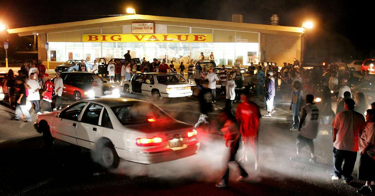 People gather to watch a sideshow at the Big Value parking in south Stockton, Calif., on Sunday, July 16, 2006. The spontaneous nature of the sideshows which are staged on interstates, in deserted parking lots, and on downtown streets keeps police guessing. Departments have spent millions in overtime policing the outlaw rallies. (AP Photo/Omar Vega)